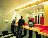 Two Businessmen Talking in a Public Lavatory Washing their Hands