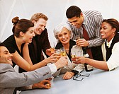 Group Portrait of Business People Sitting Behind a Table Celebrating With Glasses of Champagne