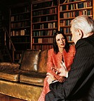 Ceo and a Businesswoman in Discussion Sitting on a Leather Sofa