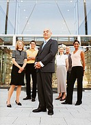 Portrait of a Group of Smiling Businessmen and Businesswomen Standing in Front of An office Building