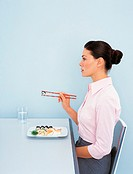 Side View of a Businesswoman Sitting at a Table With Sushi Using Chopsticks