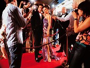 Portrait of a Couple Standing on a Red Carpet Being Photographed By Paparazzi at Night
