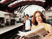Businesswoman Standing on a  Railroad Station Platform Reading a Newspaper and a Man Standing Using a Mobile Phone