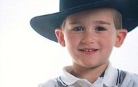 Boy wearing large black cowboy hat