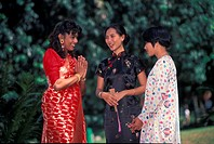 Three ladies in traditional attire greeting each other, Malaysia