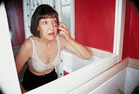 Mature woman looking at her reflection (thumbnail)