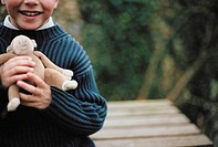 Young boy holding a toy monkey (thumbnail)