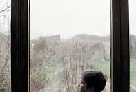 Young boy looking out of window (thumbnail)