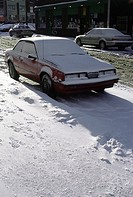 Snow-covered car parked in street (thumbnail)