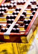 Closeup of wooden abacus laid on top of American banknotes (thumbnail)