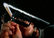 Cocaine snorting. Woman snorting a line of cocaine next to a razor blade seen from below. This alkal- oid drug comes from the leaves of the  coca  pla...