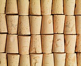Cork manufacture. Rows of freshly cut corks  for bottles. Corks are produced from the tree bark of the cork oak (Quercus suber).