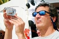 Man using video recorder. Volleypalooza Festival. Lummus Park. Ocean Drive. South Beach. Miami Beach. Florida. USA