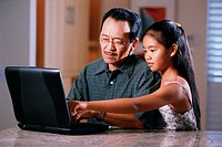 Father and daughter at laptop computer