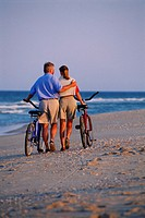 Couple with bicycles walking down beach