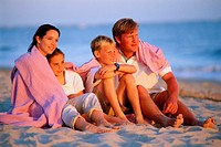 A family sitting together in the sand
