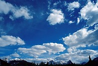 Cumulus clouds hanging low over snow covered mountains (thumbnail)