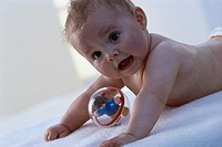 Lies, baby, bare, glass ball, child, childhood, wakened, vigorously, alertly, interests, prone position, toy, toy ball, plays, interior