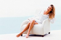 Woman sitting down on white armchair