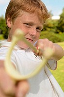 Boy aiming catapult at camera