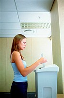 Woman feeds paper in shredder