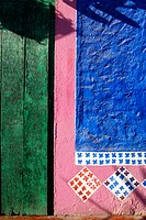 Colorful exterior of Mi Casa restaurant, green door, blue and pink wall, painted decoration. Cabo San Lucas, Mexico