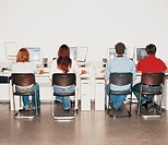 Rear View of Four Students Sitting in a Line Using Computers