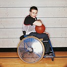 Portrait of a Teenage Boy in a Wheelchair Holding a Basketball