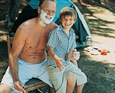 Portrait of Father and Son Camping Sitting on a Chair Wearing Shaving Foam