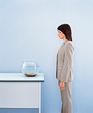 Businesswoman Looking Down at Goldfish in a Goldfish Bowl
