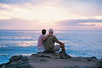 Senior Couple Sitting and Looking at the View at the Sea From a Rocky Coast