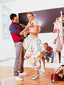 Stylist Assisting a Fashion Model in a Studio and a Photographer Crouching in the Background