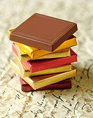 Thin chocolates stacked on florentine paper