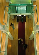 People walking inside building, view from above