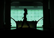 Woman walking in front of desk, silhouette, view through doorway