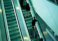 Business people on escalator going up, blurred, high angle view