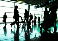 Silhouettes of business people walking in airport terminal, backlit