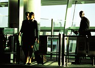 Businessman and businesswoman walking through security gate with suitcases