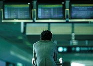 Businessman sitting under airport departure and arrival monitors, rear view