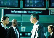 Businesspeople talking in front of an airport information sign