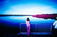 A woman views a river (infrared color)