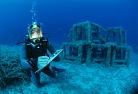 Underwater biological research. Marine biologist scuba diving to assess the state of an artificial reef. Coral and other underwater animals and plants...