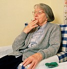 Elderly woman smoking tobacco. An elderly woman sits on a chair while smoking a cigarette. Smoking tobacco cigarettes can temporarily lift the mood by...