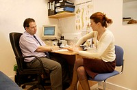 Osteopathy. Osteopath and female patient in a consultation room. The osteopath is taking a full case history before carrying out an examination on the...