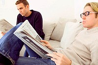 Men reading newspapers on sofa