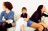 Women sitting back to back on sofa