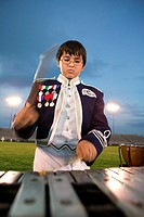 Close-up of a boy playing the xylophone chimess in the percussion section of the marching band.