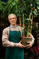 Portrait of a florist holding a potted tree.