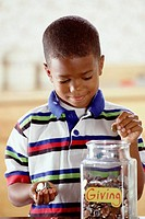 Boy Putting Money In Donation Jar