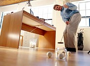 Man Playing Golf In Office